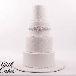 White wedding cake with bling sash